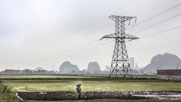 Ninh Binh, Vietnam - March 4, 2016: A farmer is working on the field at Ninh Binh, Vietnam. In the background is a  High-voltage line and the famous rocks of Ninh Binh.